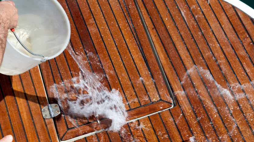 Washing-the-teak-yacht-deck-with-water-from-a-plastic-bucket.