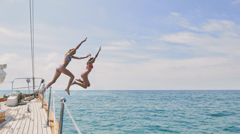 two-girls-jumping-off-boat-yacht-into-ocean-water