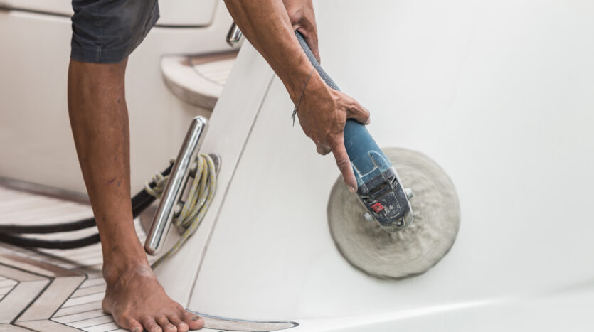 Yacht-maintenance-A-man-machine-buffing-and-polishing-side-of-the-white-boat-by-grinder-machine-in-the-marina